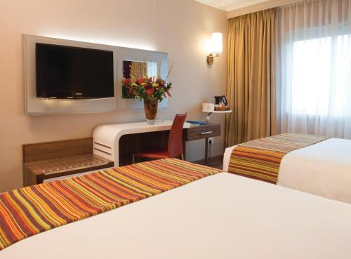 A bed or beds in a room at Garden Court Sandton City