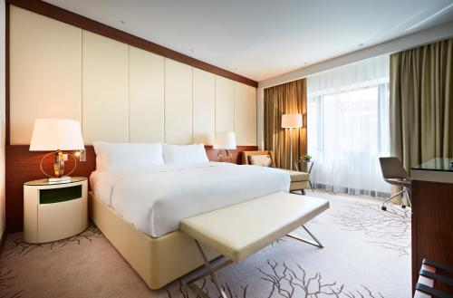A bed or beds in a room at Renaissance Minsk Hotel