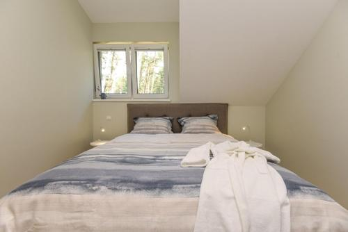 A bed or beds in a room at Preila Holiday apartment in the pine forest