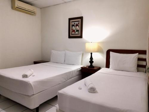 A bed or beds in a room at Hotel Armonía Hostal