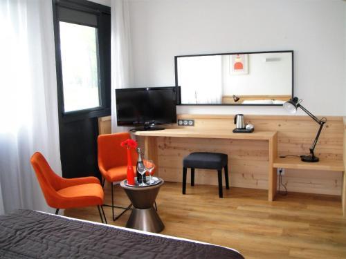 Télévision ou salle de divertissement dans l'établissement Golf Hôtel Grenoble Charmeil