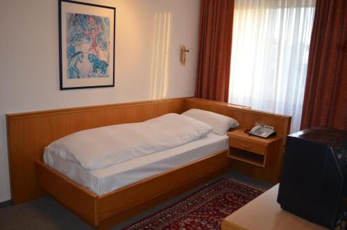 A bed or beds in a room at Hotel Drei Schweizer