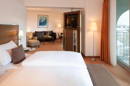 A bed or beds in a room at Dorint An der Kongresshalle Augsburg