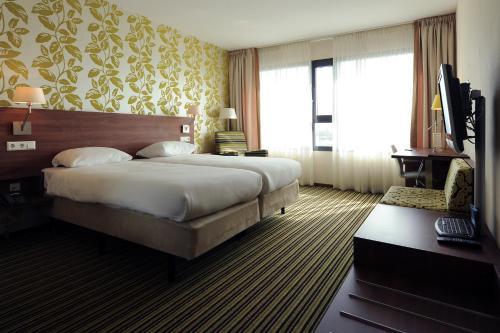 سرير أو أسرّة في غرفة في Van der Valk Hotel Rotterdam Ridderkerk