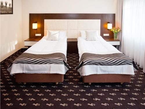 Łóżko lub łóżka w pokoju w obiekcie Hotel Fryderyk