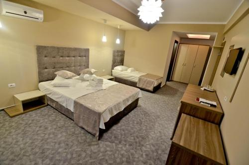 A bed or beds in a room at Lucas Boutique Hotel