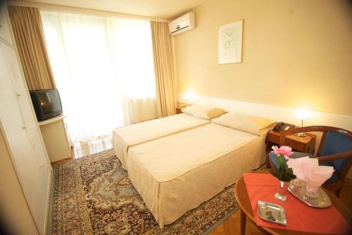 Un pat sau paturi într-o cameră la Hotel Astoria