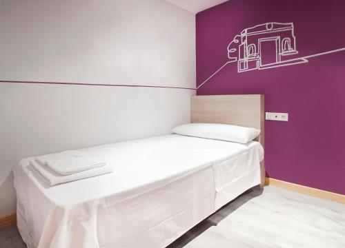 A bed or beds in a room at Hostal Herradores