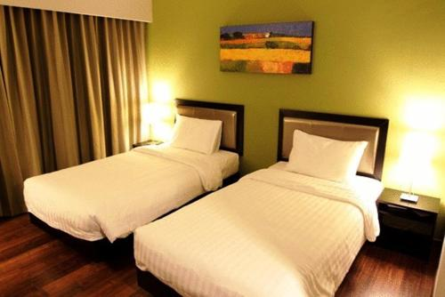 A bed or beds in a room at The Brunei Hotel
