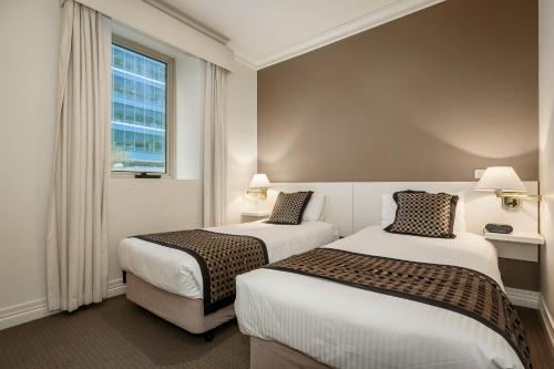 A bed or beds in a room at Quest On Lonsdale