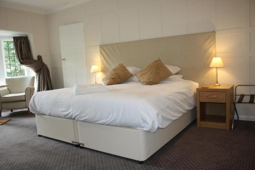 A bed or beds in a room at East Cliff Cottage Hotel