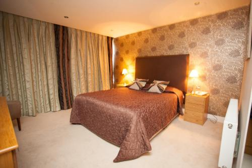A bed or beds in a room at Earl of Desmond Hotel