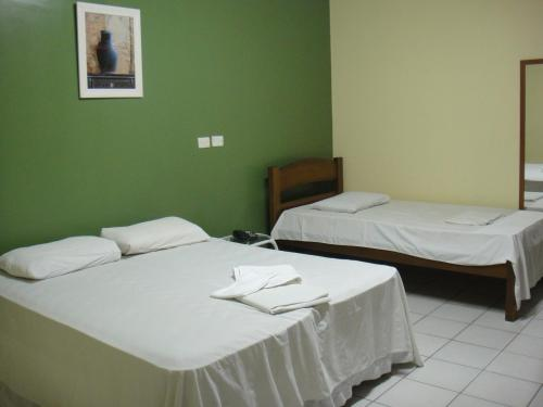 A bed or beds in a room at Ouro Hotel