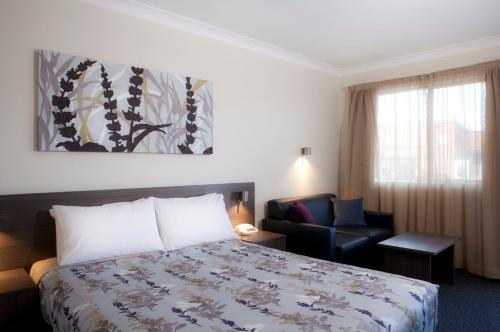 A bed or beds in a room at Narellan Motor Inn