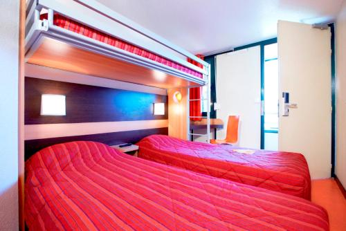 A bed or beds in a room at Premiere Classe Metz Nord - Semecourt