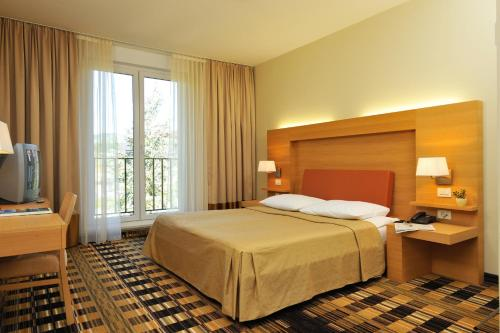 A bed or beds in a room at Hotel Smarjeta - Terme Krka