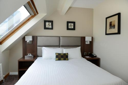 A bed or beds in a room at Ramada Telford Ironbridge