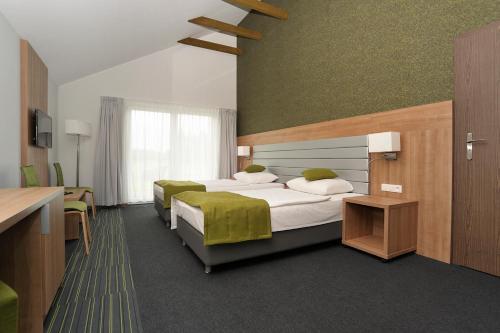 Łóżko lub łóżka w pokoju w obiekcie Kalinowe Pola Golf Village