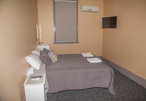 A bed or beds in a room at Hotel Cessnock