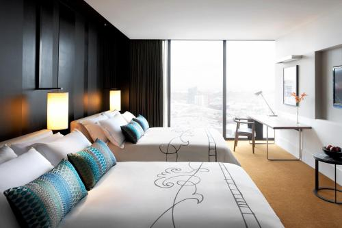 A bed or beds in a room at Crown Metropol Melbourne