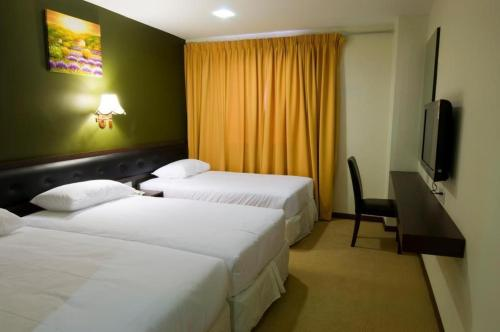 A bed or beds in a room at Syaz Meridien Hotel