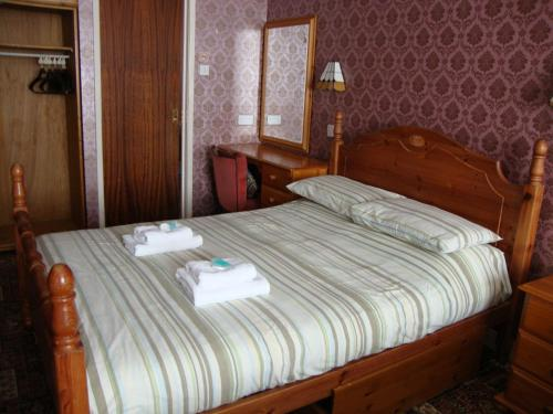 A bed or beds in a room at Mayfield Hotel