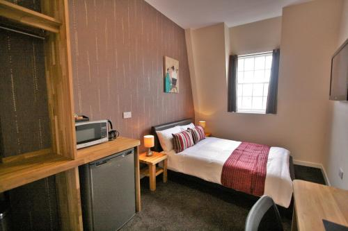 A bed or beds in a room at Central Hotel Gloucester by RoomsBooked