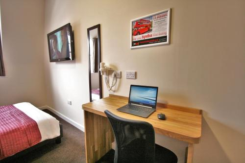 A television and/or entertainment center at Central Hotel Gloucester by RoomsBooked