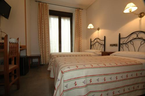 A bed or beds in a room at Hostal Ivor