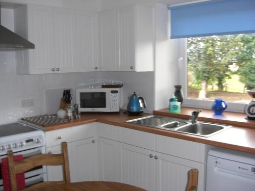A kitchen or kitchenette at Seggat Farm Holiday Cottages