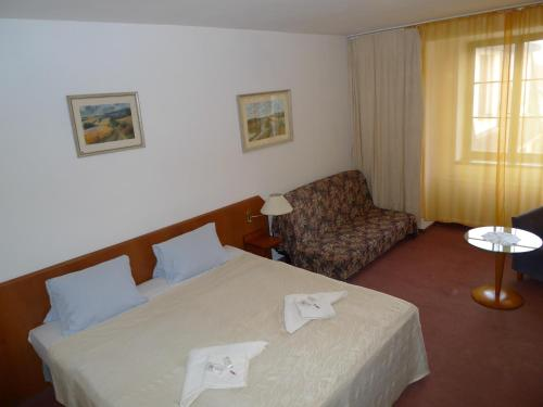 A bed or beds in a room at Hotel Prokop
