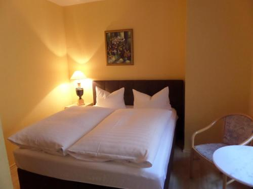 A bed or beds in a room at Hotel Am Sudenburger Hof