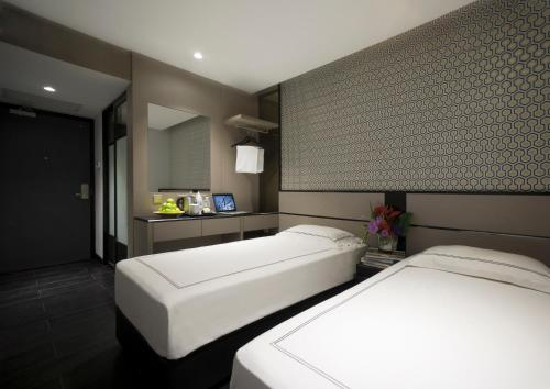 A bed or beds in a room at Venue Hotel The Lily (SG Clean)