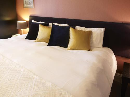 A bed or beds in a room at Charlton Kings Hotel