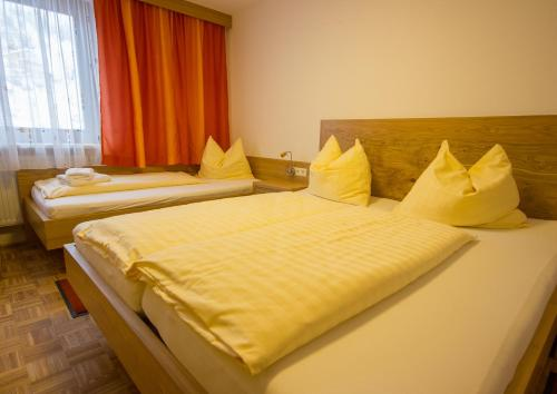 A bed or beds in a room at Café Pension Alpina