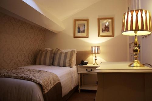 A bed or beds in a room at The Georgian Town House Hotel
