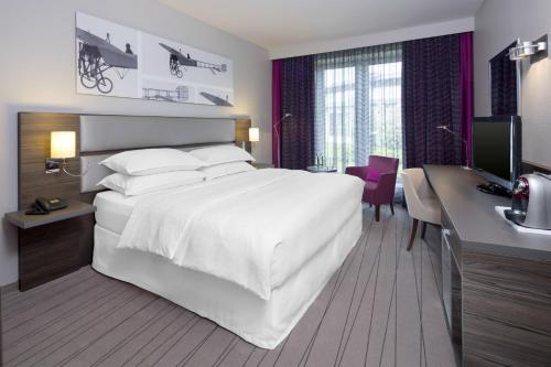 A bed or beds in a room at Sheraton Duesseldorf Airport Hotel