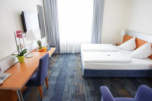 A bed or beds in a room at Senator Hotel