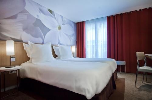 A bed or beds in a room at Hôtel Albe Saint Michel