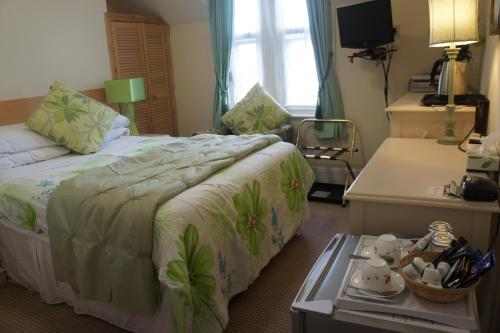 A bed or beds in a room at Athena Guest House