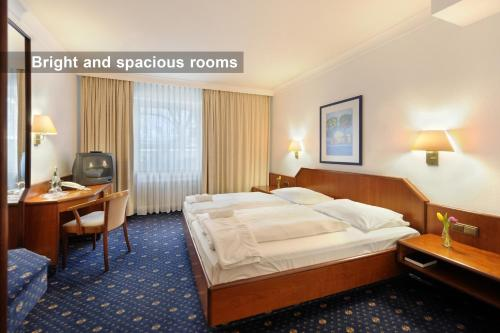 A bed or beds in a room at Ambassador Parkhotel