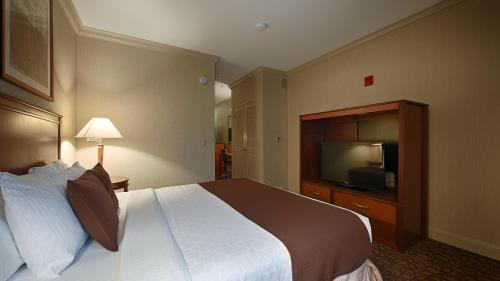 A bed or beds in a room at Best Western Plus All Suites Inn