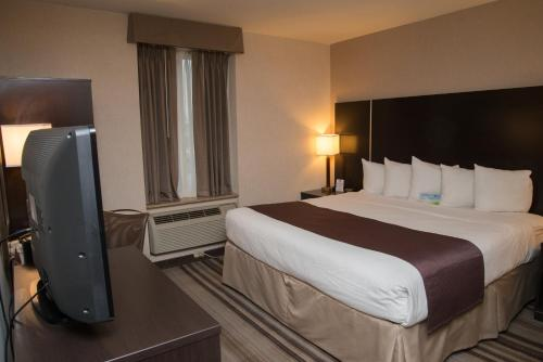 A bed or beds in a room at Days Inn by Wyndham Jamaica / JFK Airport