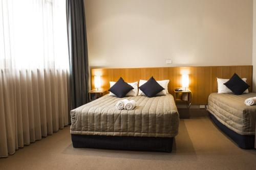 A bed or beds in a room at Central Hotel Hobart
