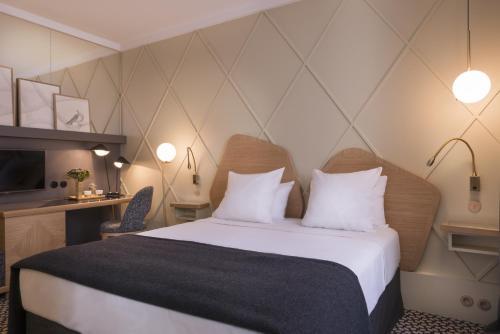 A bed or beds in a room at Millésime Hôtel