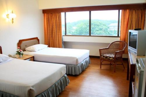 A bed or beds in a room at Thumrin Hotel