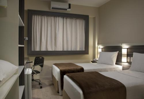 A bed or beds in a room at Master Express Dom Pedro II - Aeroporto
