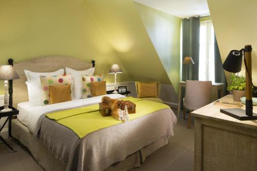 A bed or beds in a room at Hotel Le Petit Chomel