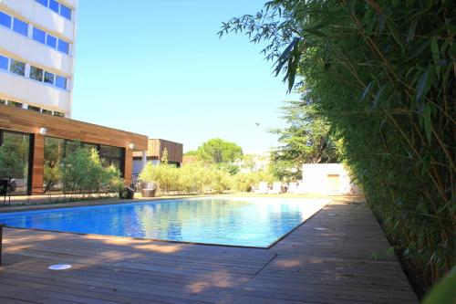 The swimming pool at or close to HÔTEL C SUITES**** chambres spacieuses, séjours thématiques