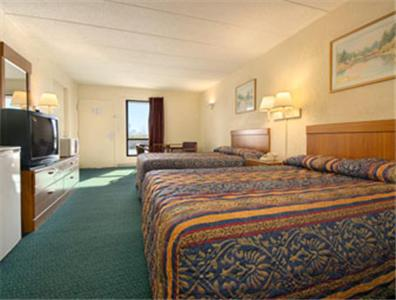 A bed or beds in a room at Days Inn by Wyndham Cincinnati East